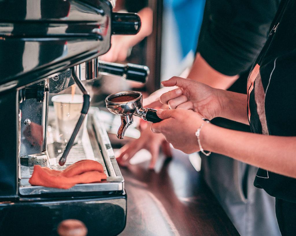 Barista na evencie przygotowuje kawę w ekspresie