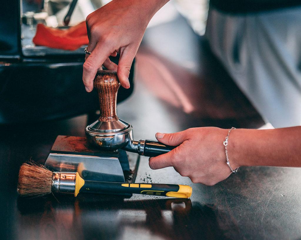 Barista na targach przygotowuje kawę w ekspresie ciśnieniowym